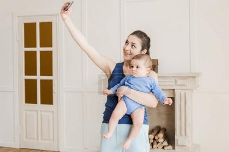 Photo pour Mère souriante prenant selfie sur smartphone avec son fils à la maison - image libre de droit