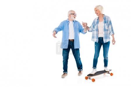 Senior couple skateboarding