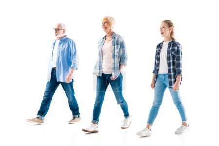 Photo for Happy grandfather, grandmother and granddaughter walking together isolated on white - Royalty Free Image