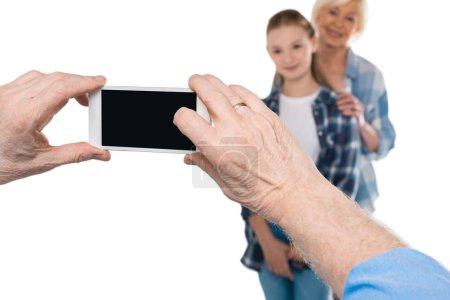 Grandfather taking photo on smartphone