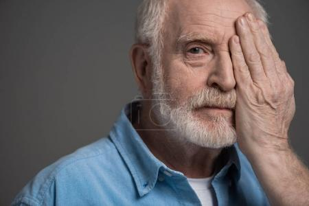 Photo for Portrait of senior bearded man reviewing eyesight isolated on grey in studio - Royalty Free Image