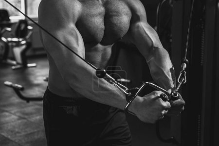 Photo for Cropped view of muscular bodybuilder working out with sport equipment in gym, black and white - Royalty Free Image