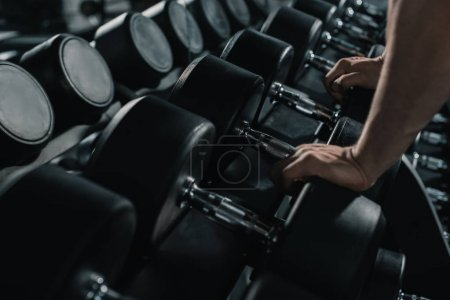 Photo for Cropped view of muscular sportsman with big dumbbells in sports center - Royalty Free Image