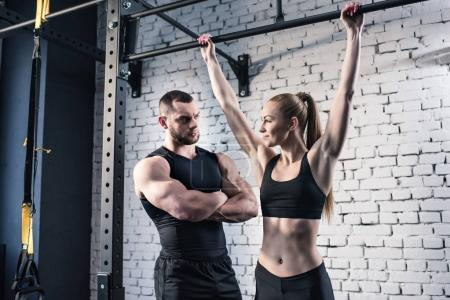 Photo for Athletic man and woman in sportswear exercising together in gym - Royalty Free Image