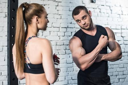 Photo for Muscular young man showing biceps to sporty young woman - Royalty Free Image