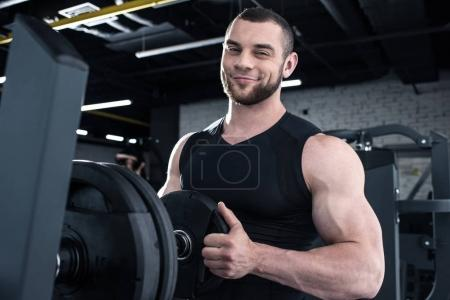 Photo for Smiling muscular man putting weight on dumbbell and looking at camera in gym - Royalty Free Image