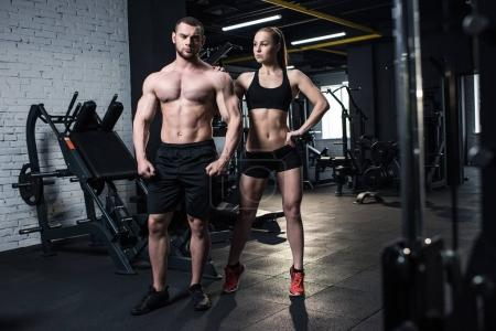 Photo for Young fit couple in sportswear posing together at gym - Royalty Free Image