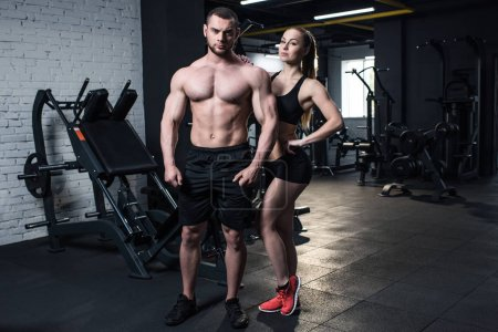 sportive couple posing at gym