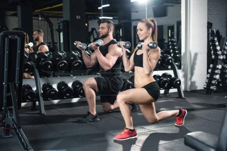 Photo for Side view of couple exercising with dumbbells together at gym - Royalty Free Image