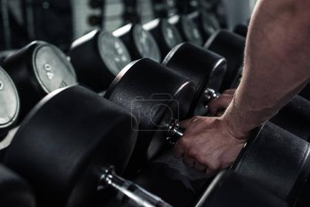 Photo for Partial view of man taking dumbbells for exercising at gym - Royalty Free Image