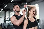 instructor helping young woman at gym