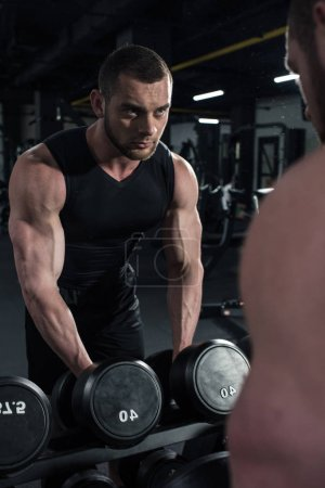 sportsman holding dumbbells while looking at mirror