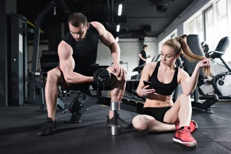 Photo for Man training with dumbbell while woman using smartphone at gym - Royalty Free Image