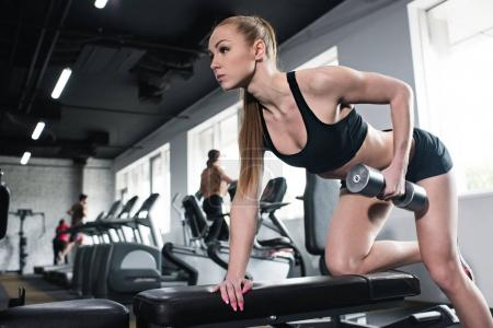 Young woman training with dumbbell at gym
