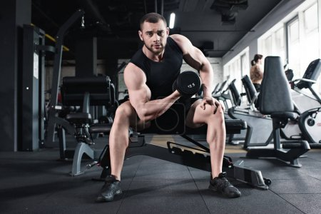 Sportsman doing biceps workout with dumbbell