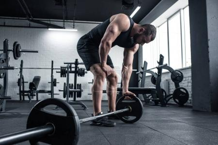 exhausted bodybuilder holding barbell at gym