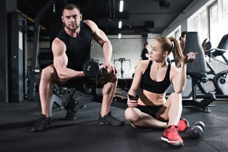 Photo for Man training with dumbbell while woman holding smartphone at gym - Royalty Free Image