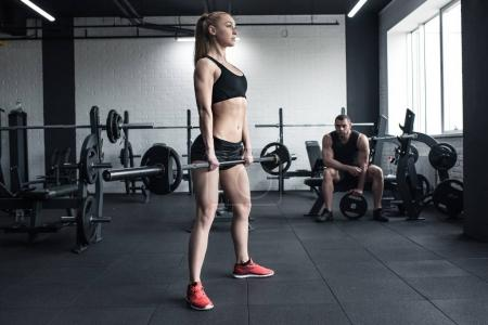 Photo for Woman doing strength training with barbell while man sitting at gym - Royalty Free Image