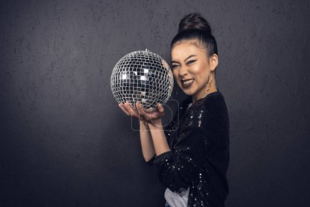 Photo for Glamour cheerful asian girl holding disco ball and posing at grey wall in studio - Royalty Free Image