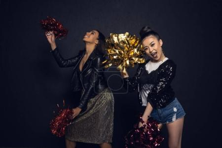 Photo for Carefree stylish young women having fun with pom-poms isolated on black - Royalty Free Image
