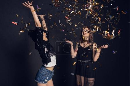 Photo for Carefree stylish young women having fun with confetti isolated on black - Royalty Free Image