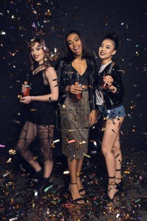 Photo pour Souriant jeunes femmes élégantes tenant des bouteilles et faire la fête avec des confettis brillants - image libre de droit