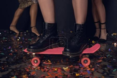 Photo pour Vue partielle de la femme debout sur le skateboard avec des amis derrière pendant la fête - image libre de droit