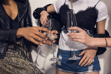 Photo for Cropped shot of young girls pouring champagne into glasses at party - Royalty Free Image