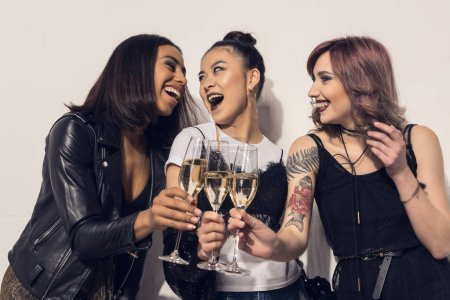 Photo for Young happy multiethnic girls drinking champagne at party - Royalty Free Image