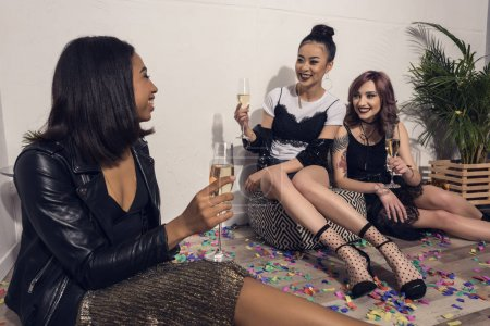 multiethnic girls sitting and drinking champagne