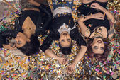 multiethnic girls lying on floor with confetti