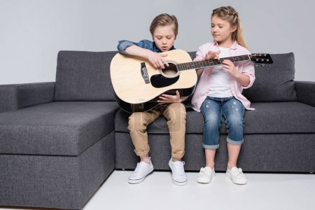 Photo for Focused brother and sister playing on guitar together while sitting on sofa - Royalty Free Image