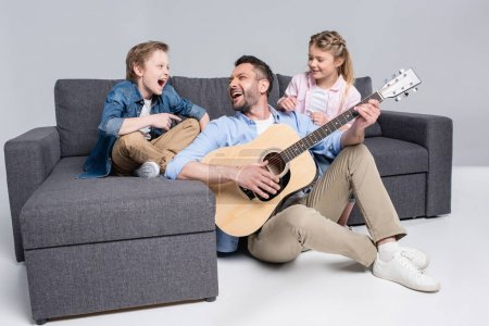 happy family playing on guitar