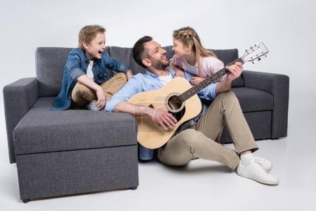 Photo pour Famille heureuse jouant à la guitare et chantant, passer du temps ensemble tout en étant assis sur le canapé - image libre de droit