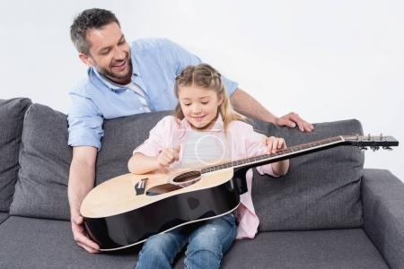 father with daughter playing on guitar