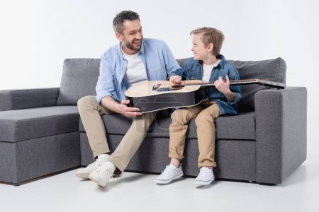 father with son playing on guitar