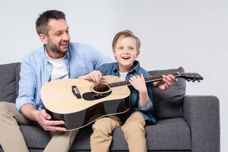 Photo pour Père souriant enseignant à son fils excité à chanter et à jouer à la guitare - image libre de droit