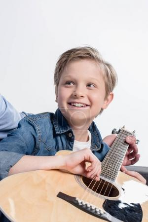 boy practicing to play on guitar