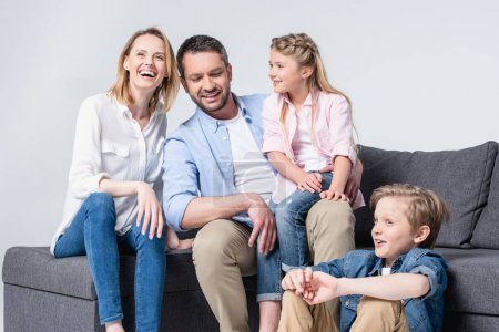 Photo for Happy young family with two children sitting together on sofa and smiling - Royalty Free Image