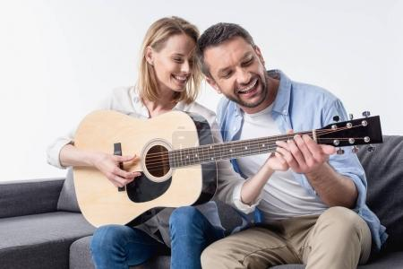 Photo for Smiling man teaching woman playing acoustic guitar isolated on white - Royalty Free Image