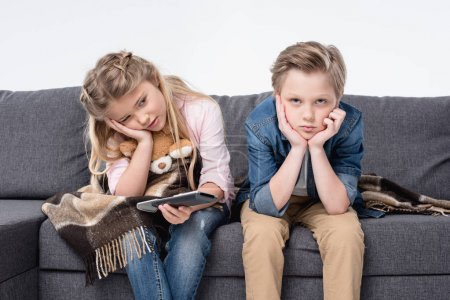 Photo for Pre-adolescent bored brother and sister sitting on sofa and holding remote control - Royalty Free Image
