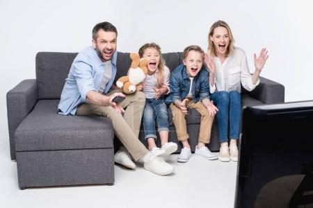 family watching tv while sitting on sofa