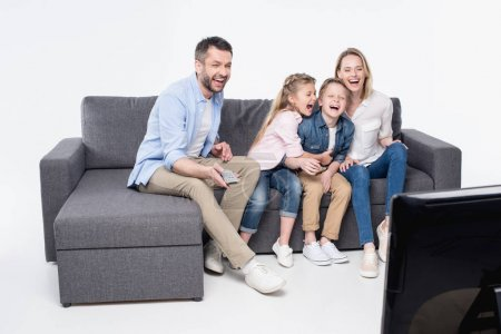 Family sitting on sofa and watching tv