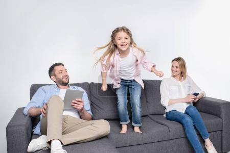 Photo for Father and mother sitting while little daughter jumping at sofa - Royalty Free Image