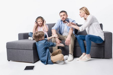 family sitting on sofa with digital devices