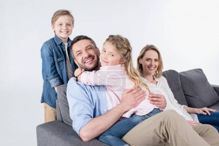 family looking at camera while sitting on sofa