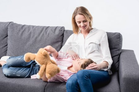 Mother with little daughter sitting on sofa