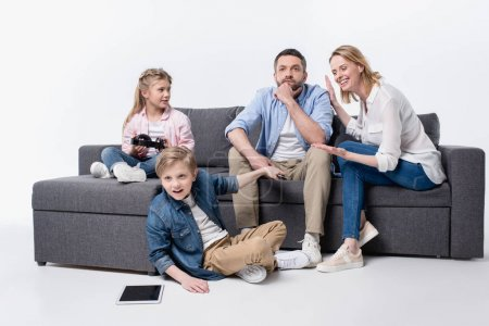 caucasian family sitting on sofa together