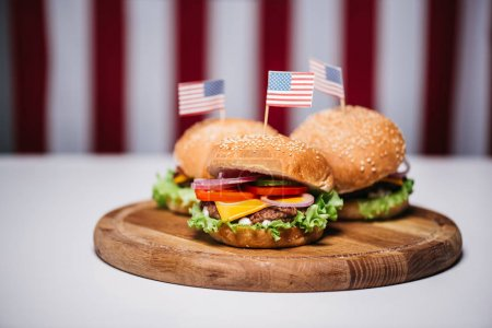 Photo for Three cheeseburgers with little american flags on wooden board, us flag on background, american culture concept - Royalty Free Image