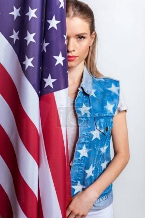 Photo pour Jolie fille blonde debout avec drapeau américain et regardant la caméra - image libre de droit